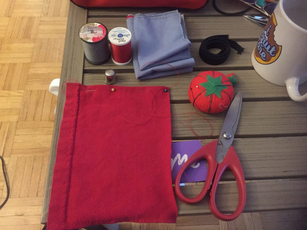 Two spools of thread, fabric, elastic, a thimble, a pincushion, the working fabric, and scissors.
